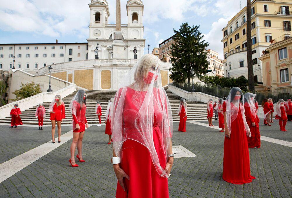 Le donne vestite di rosso  partecipano a una azione per attirare l'attenzione pubblica al problema di violenza sulle donne in occasione della Giornata internazionale per l'eliminazione della violenza contro le donne, 26 ottobre 2020, Roma, Italia.