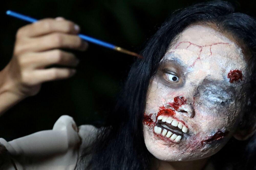 La venditrice di vestiti online, Kanittha Thongnak, applica il trucco di Halloween prima di iniziare la diretta per vendere vestiti di persone morte a Bangkok, Thailandia, 10 ottobre 2020.