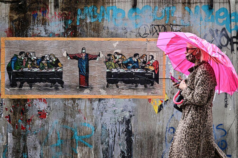 Una donna in mascherina di colore leopardato sullo sfondo di murale realizzato da un artista italiano TvBoy, Milano, 27 ottobre 2020.