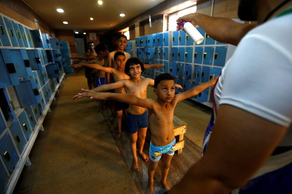 Disinfezione dei bambini prima della lezione nella piscina a Kerbala, Iraq, 20 ottobre 2020.