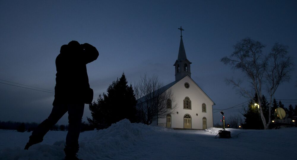 A journalist takes a photo of the church in La Motte, Quebec, at twilight Wednesday, 13 March 2013, in La Motte. THE CANADIAN PRESS/Adrian Wyld