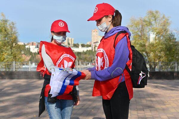 I volontari distribuiscono bandiere tricolori in occasione della Giornata dell'Unità Nazionale nel Parco Levoberezhny a Rostov sul Don, Russia.  - Sputnik Italia