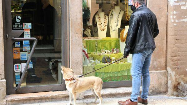 Un uomo con cane vicino a un negozio - Sputnik Italia