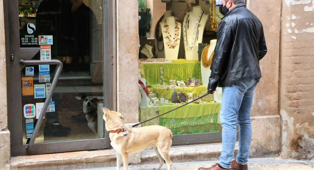 Un uomo con cane vicino a un negozio