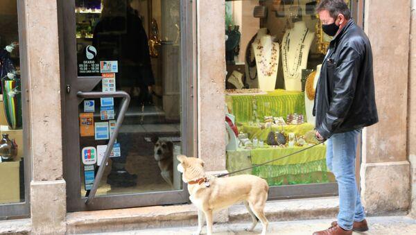 Un uomo in mascherina con cane vicino a un negozio - Sputnik Italia