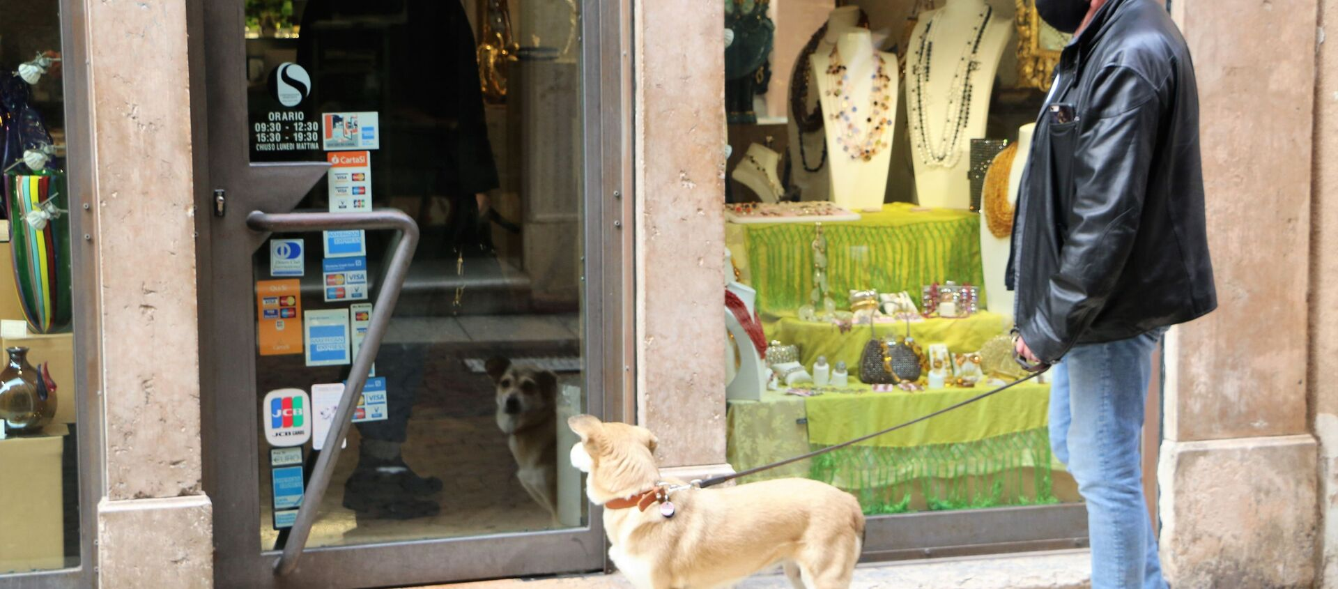 Un uomo in mascherina con cane vicino a un negozio - Sputnik Italia, 1920, 14.02.2021