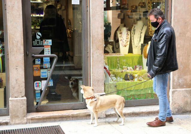 Un uomo in mascherina con cane vicino a un negozio