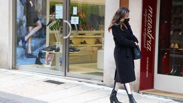 Una donna in mascherina vicino a un negozio - Sputnik Italia