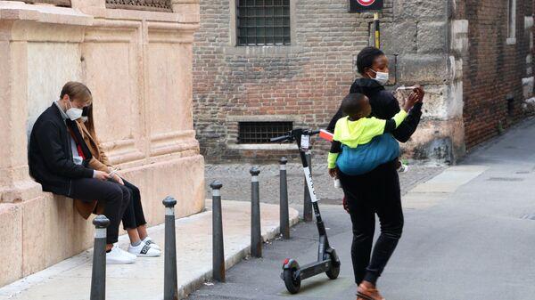 Una donna  in mascherina con bambino - Sputnik Italia