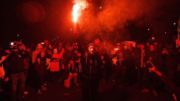 An anti-capitalist protester wearing aGuy Fawkes mask holds a lit flare during the Million Masks March, organised by the group Anonymous, near the Houses of Parliament in central London on November 5, 2015. - Sputnik Italia