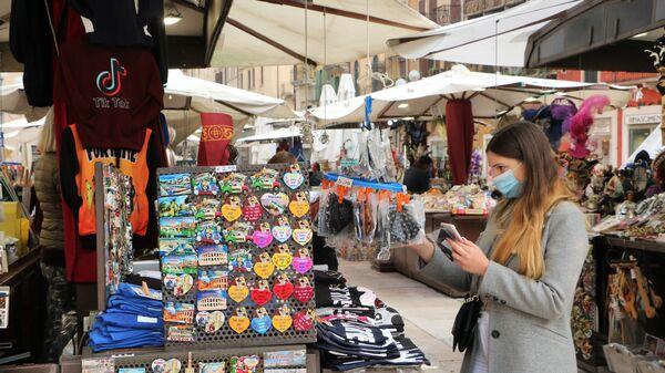 Una ragazza in mascherina compra i souvenir  - Sputnik Italia