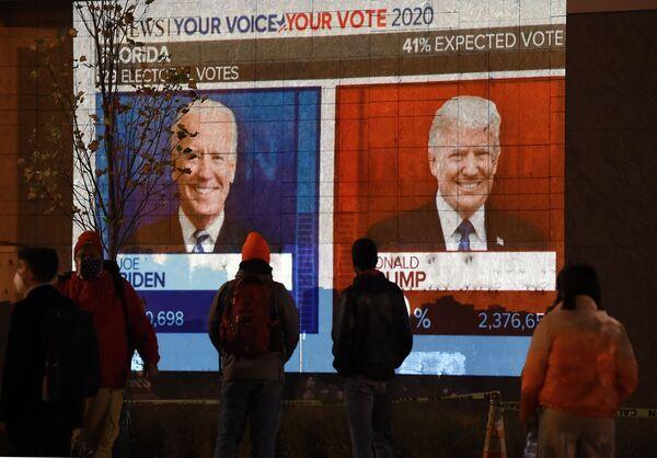 La gente guarda un grande schermo che mostra i risultati delle elezioni in diretta in Florida nella piazza Black Lives Matter, il 3 novembre 2020 - Sputnik Italia