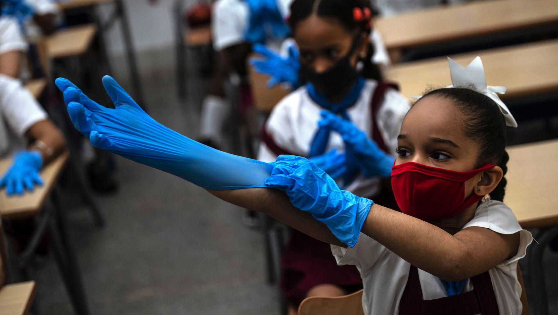 Ученица школы в защитных перчатках и маске в школе, Гавана  - Sputnik Italia, 1920, 09.05.2021