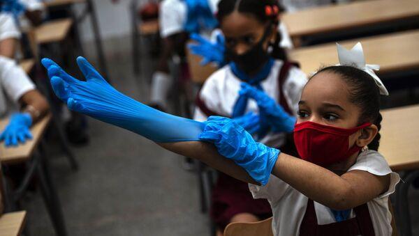 Ученица школы в защитных перчатках и маске в школе, Гавана  - Sputnik Italia