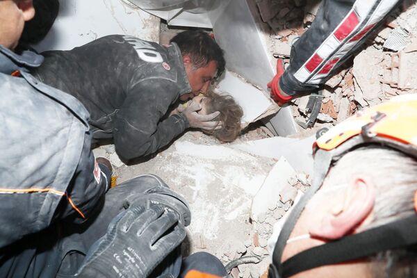 I soccorritori tirano fuori una bambina di 4 anni dalle macerie di un edificio crollato dopo un terremoto nella città portuale di Izmir, in Turchia, il 3 novembre 2020 - Sputnik Italia
