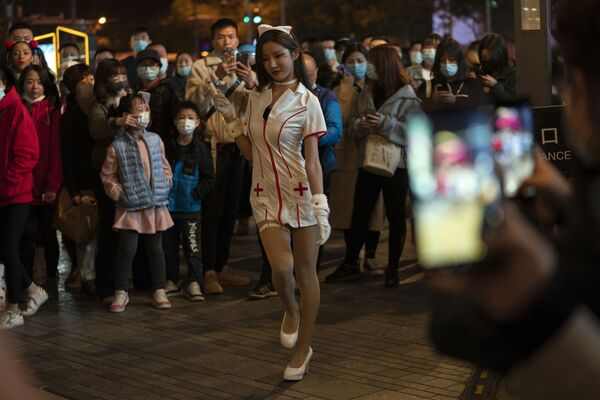 Una giovane donna vestita da infermiera si esibisce mentre una folla si è radunata durante la notte di Halloween in un quartiere dello shopping a Pechino sabato il 31 ottobre 2020 - Sputnik Italia