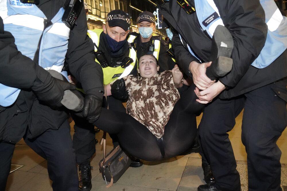 Un manifestante anticapitalista viene arrestato da alcuni agenti di polizia a Oxford Street nel corso della Marcia del Milione di Maschere, organizzata dal gruppo Anonymous a Londra il 5 novembre 2020.