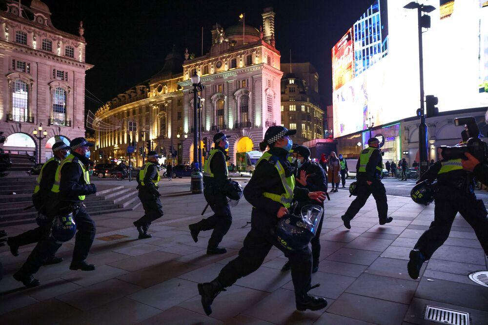Gli agenti di polizia stanno inseguendo i manifestanti durante la Marcia del Milione di Maschere a Londra, il 5 novembre 2020.