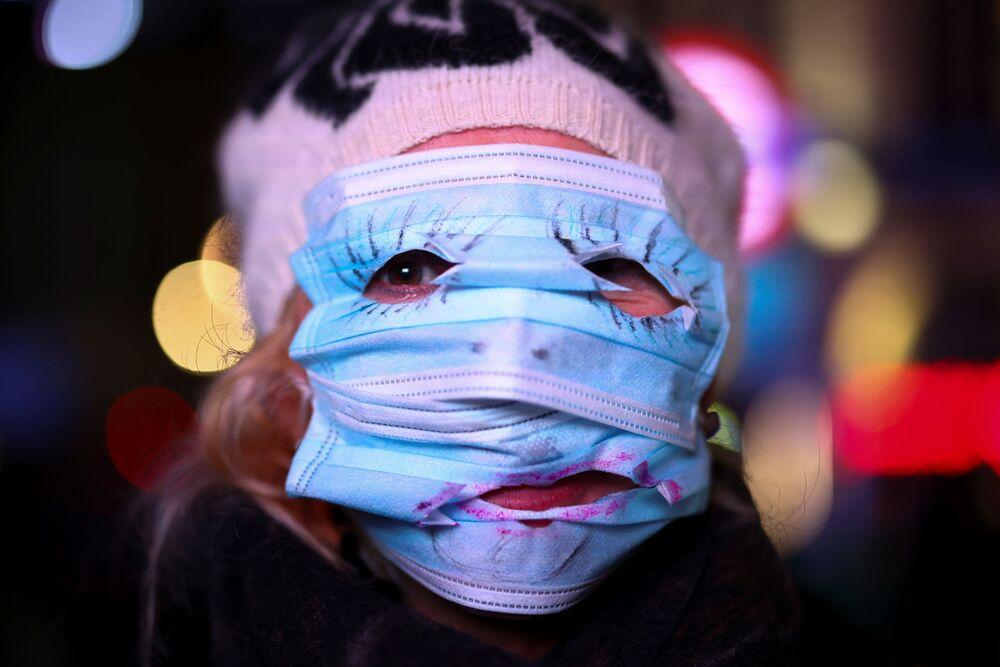 Una donna usa la mascherina per nascondere la sua faccia durante la manifestazione la Marcia del Milione di Maschere a Londra.