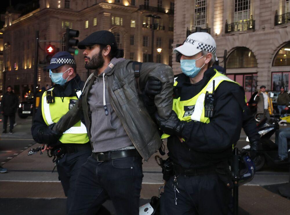 Gli agenti di polizia arrestano un manifestante durante la Marcia del Milione di Maschere a Londra, il 5 novembre 2020.