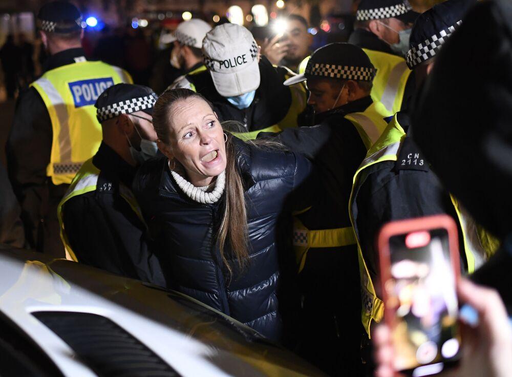 Gli agenti di polizia arrestano una donna durante la Marcia del Milione di Maschere a Londra, il 5 novembre 2020.