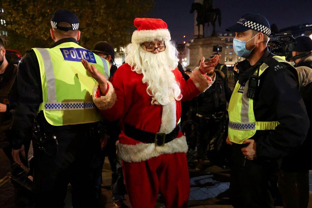 Un uomo vestito da Babbo Natale posa per la foto vicino agli agenti di polizia durante la Marcia del Milione di Maschere a Londra, il 5 novembre 2020.