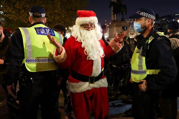 Un uomo vestito da Babbo Natale posa per la foto vicino agli agenti di polizia durante la Marcia del Milione di Maschere a Londra, il 5 novembre 2020.  - Sputnik Italia