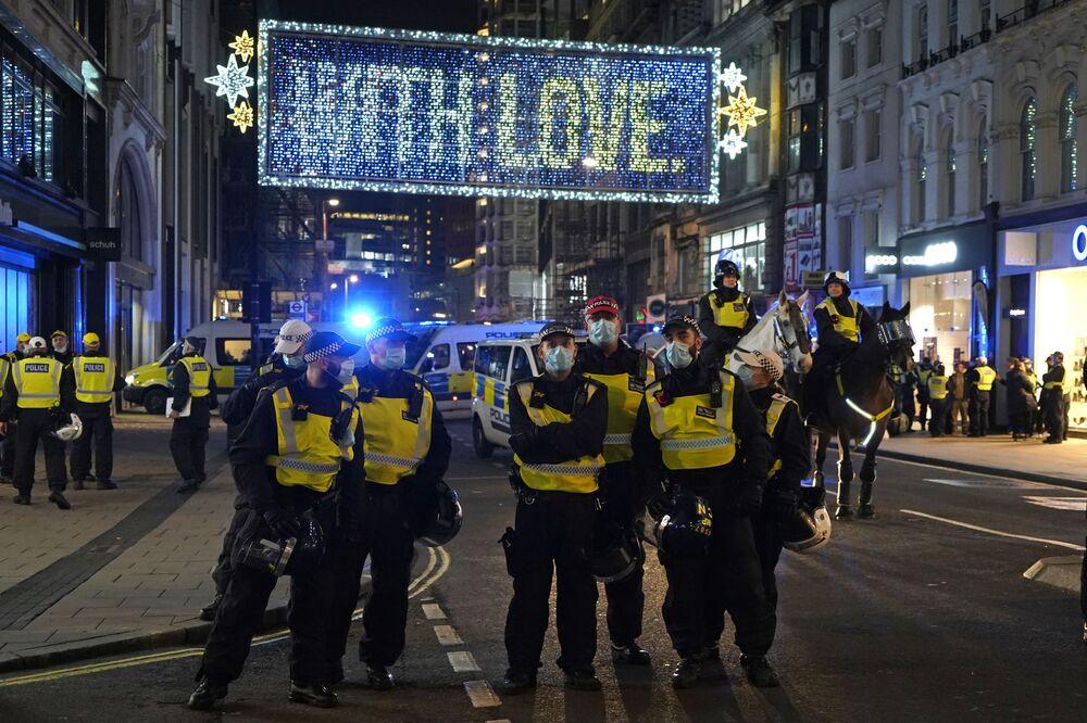 Gli agenti di polizia bloccano Oxford Street per controllare la manifestazione Marcia del Milione di Maschere a Londra, il 5 novembre 2020.