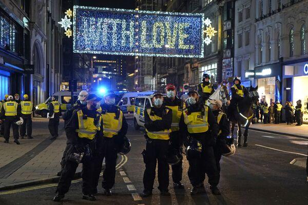 Gli agenti di polizia bloccano Oxford Street per controllare la manifestazione Marcia del Milione di Maschere a Londra, il 5 novembre 2020. - Sputnik Italia