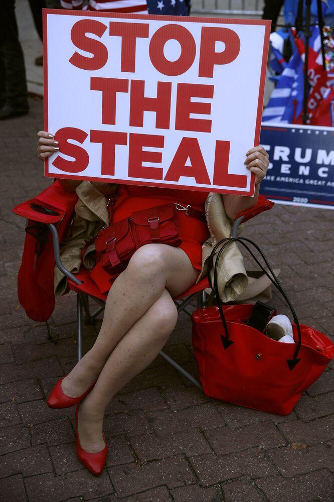 Una manifestante con un cartello Frenate il furto fuori dal Philadelphia Convention Center