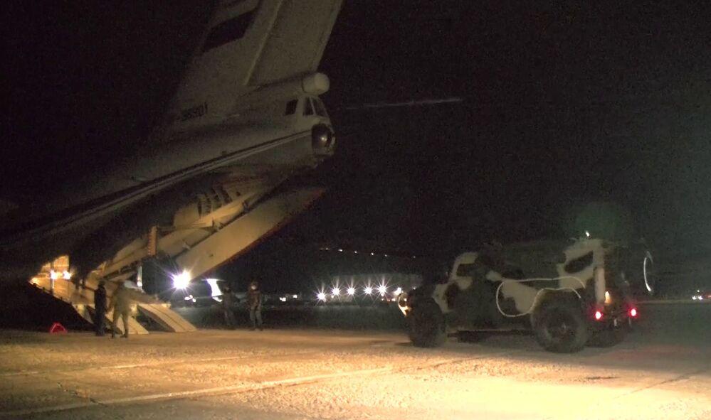 La foto mostra un SUV militare e un gruppo di soldati trasportati su un aereo da carico Il-76, parte del contingente russo di peacekeeping che comprende 1.960 militari, 90 corazzati da trasporto, oltre a 380 unità automobilistiche e di attrezzature speciali