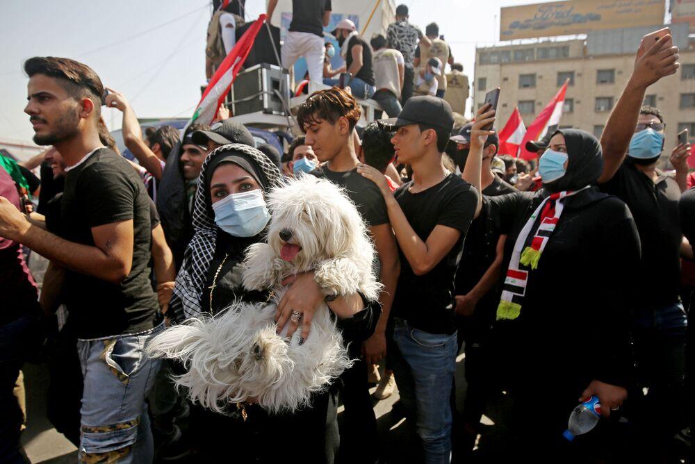 Una ragazza con un cane durante le proteste a Baghdad, in Iraq
