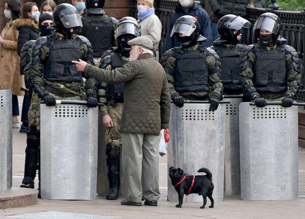 Un uomo parla con gli agenti di polizia durante una manifestazione dell'opposizione Ultimatum del popolo a Minsk - Sputnik Italia