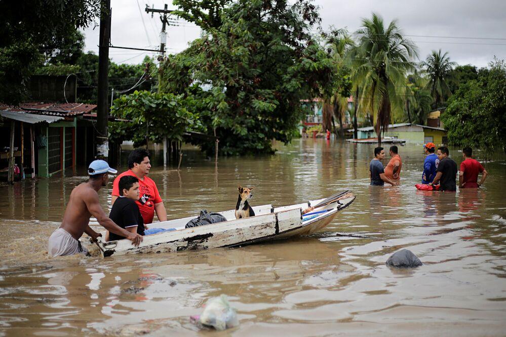 Le persone spingono una barca con un cane attraverso una strada allagata durante il passaggio di Storm Eta, a La Lima, Honduras, il 5 novembre 2020