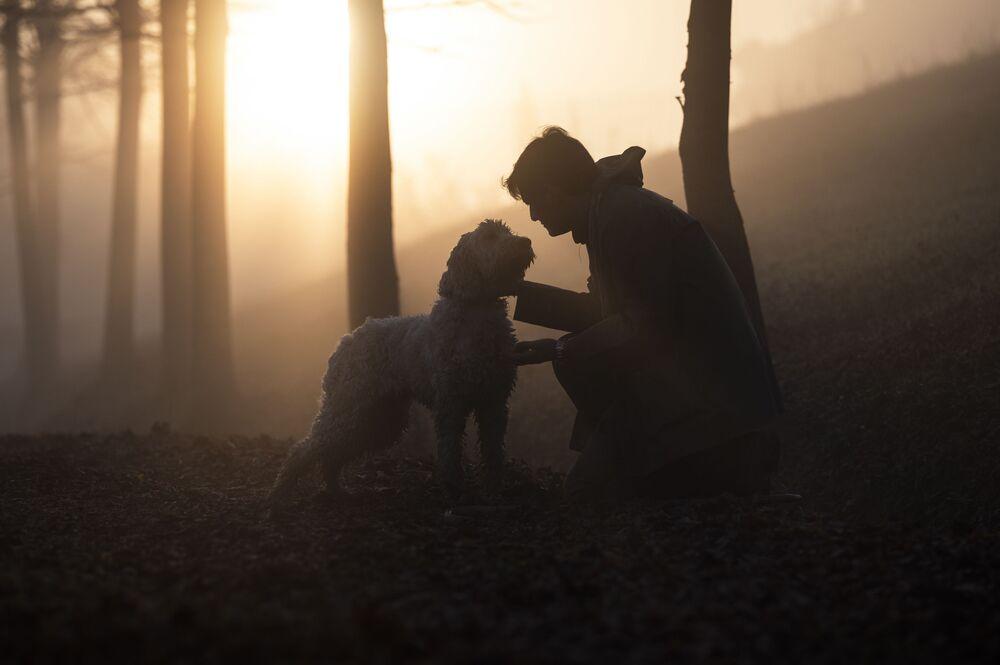 Uomo con cane nella foresta autunnale, Italia