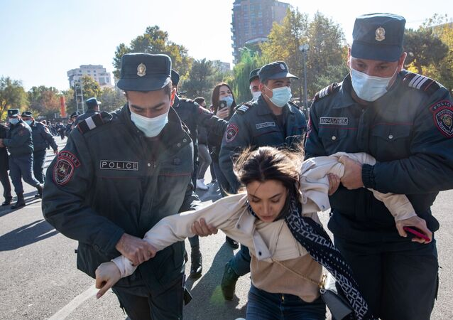 Police officers detain a demonstrator during a protest, which was organized by 17 opposition parties, against the prime minister's decision to sign a ceasefire deal with Baku , at Independance Square, in Yerevan, Armenia