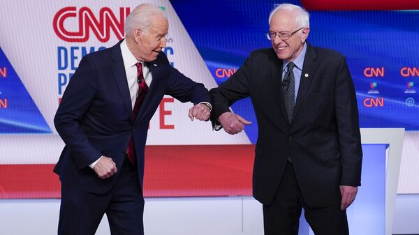 Former Vice President Joe Biden, left, and Sen. Bernie Sanders, I-Vt., right, greet one another before they participate in a Democratic presidential primary debate at CNN Studios in Washington, Sunday, March 15, 2020 - Sputnik Italia