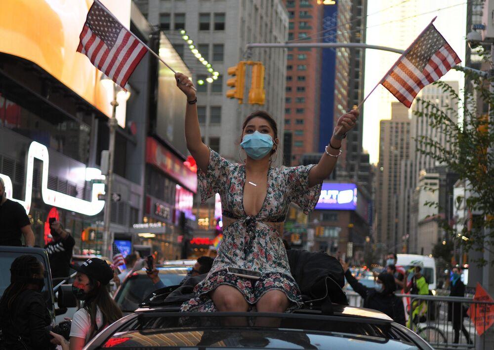 Una ragazza in una strada a New York dopo l'annuncio della vittoria di Joe Biden alle presidenziali degli USA.