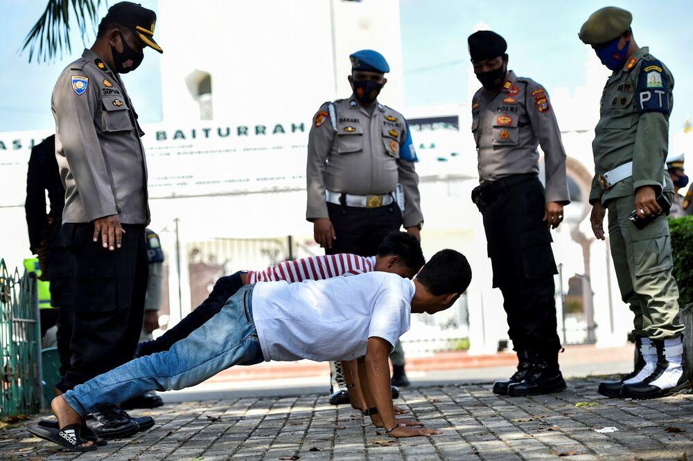 I residenti dell'Indonesia fanno esercizi fisici come punizione per la mancanza delle mascherine protettive contro il coronavirus, Banda Aceh, Indonesia, il 10 Novembre 2020.
