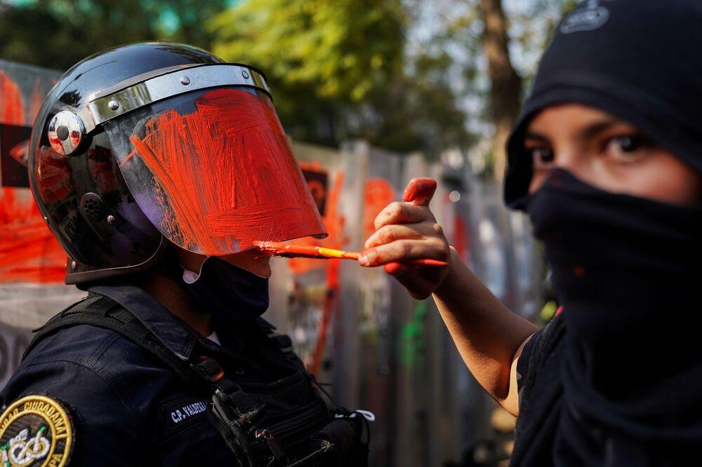 Una ragazza tinge il casco di un agente della polizia nel corso di una manifestazione contro la violenza di genere e della polizia alla città di Messico, 11 Novembre 2020.