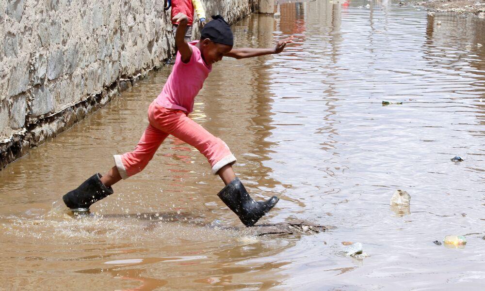 Una bambina salta in una strada innondata dopo che il livello dell'acqua del lago Naivasha ha raggiunto il record, Kenya, il 8 Novembre 2020.