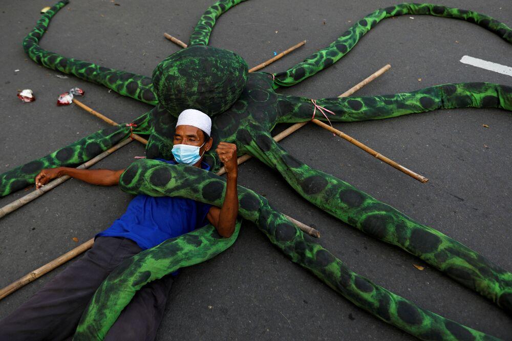Un pescatore in mascherina si sdraia su un polpo artificiale durante una protesta a Jakarta, Indonesia.