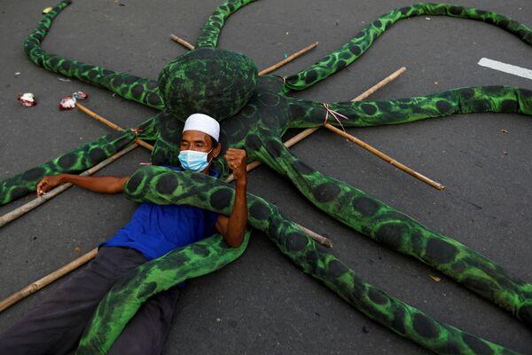 Un pescatore in mascherina si sdraia su un polpo artificiale durante una protesta a Jakarta, Indonesia. - Sputnik Italia