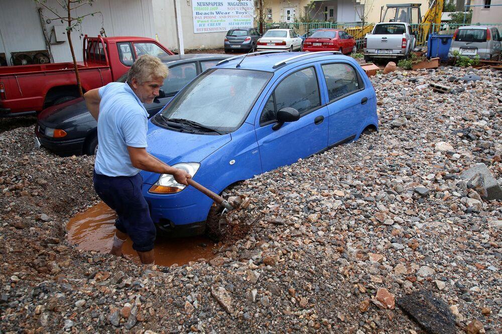 Un uomo cerca di tirare fuori la sua macchina dopo i rovesci a Malia nell'isola di Creta, Grecia, il 10 Novembre 2020.