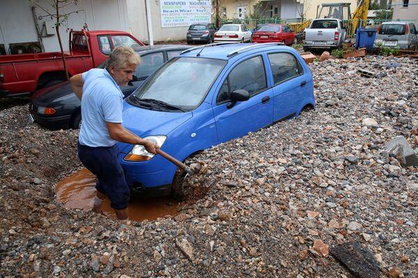 Un uomo cerca di tirare fuori la sua macchina dopo i rovesci a Malia nell'isola di Creta, Grecia, il 10 Novembre 2020.  - Sputnik Italia