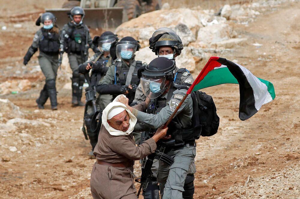 Un manifestante palestinese e agenti della polizia di frontiera israeliana durante una protesta contro gli insediamenti ebraici a Beit Dagan, Cisgiordania, il 6 novembre 2020.