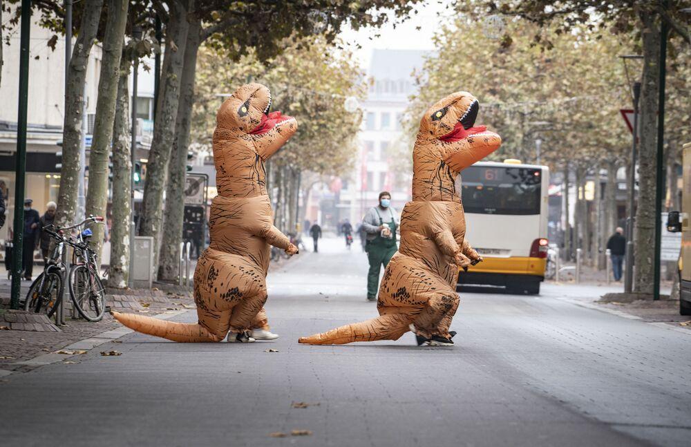 Due persone vestite da dinosauri attraversano una strada vicino alla Schillerplatz a Magonza, in Germania, L'11 novembre 2020. L'11 novembre segna l'inizio della stagione del carnevale in alcune regioni della Germania ma a causa della pandemia di Coronavirus, l'attuale stagione del carnevale è sospesa.