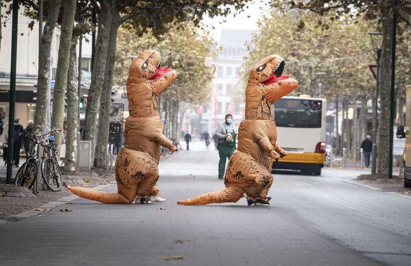 Due persone vestite da dinosauri attraversano una strada vicino alla Schillerplatz a Magonza, in Germania, L'11 novembre 2020. L'11 novembre segna l'inizio della stagione del carnevale in alcune regioni della Germania ma a causa della pandemia di Coronavirus, l'attuale stagione del carnevale è sospesa. - Sputnik Italia