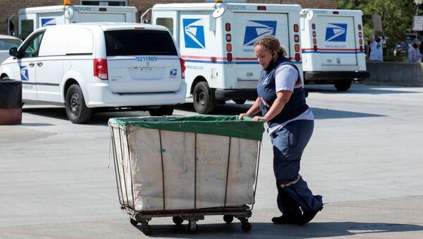 Un lavoratore del servizio postale degli Stati Uniti (USPS) spinge un carrello della posta fuori da un ufficio postale a Royal Oak, Michigan, Stati Uniti 22 agosto 2020 - Sputnik Italia