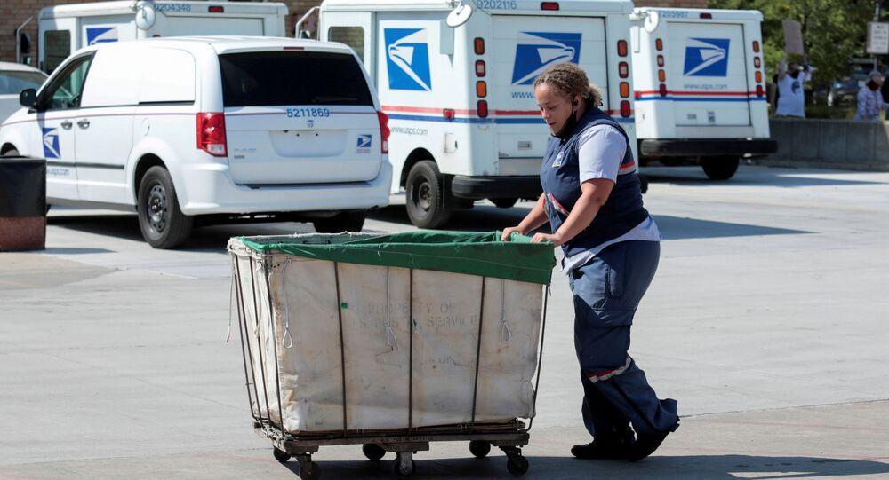 Un lavoratore del servizio postale degli Stati Uniti (USPS) spinge un carrello della posta fuori da un ufficio postale a Royal Oak, Michigan, Stati Uniti 22 agosto 2020